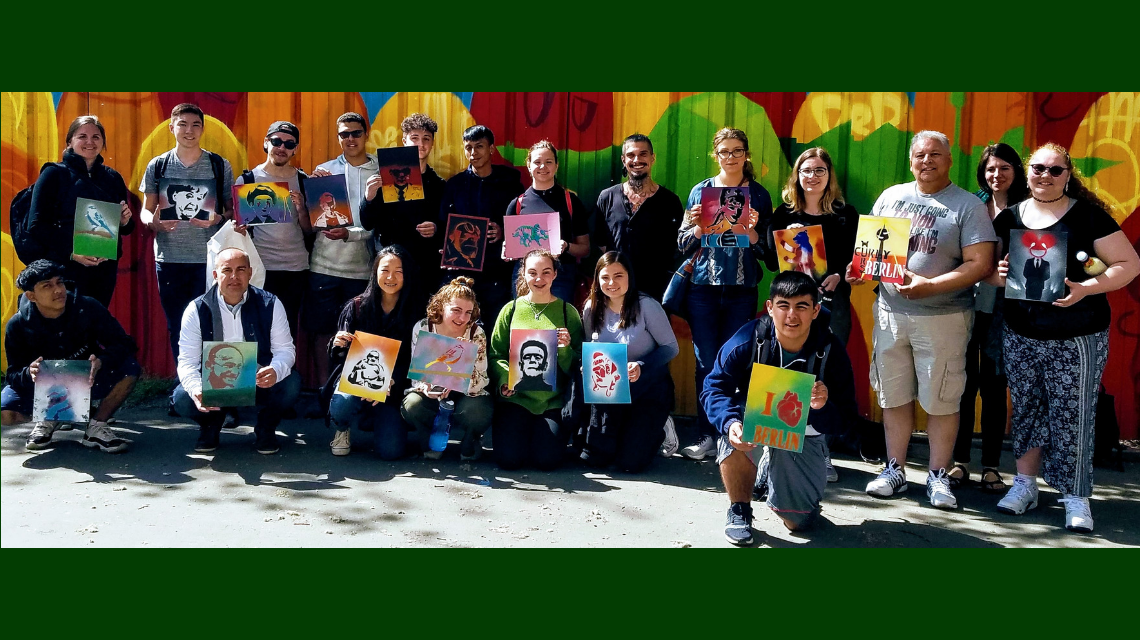 Participants in the Berlin trip pose with painting they created.